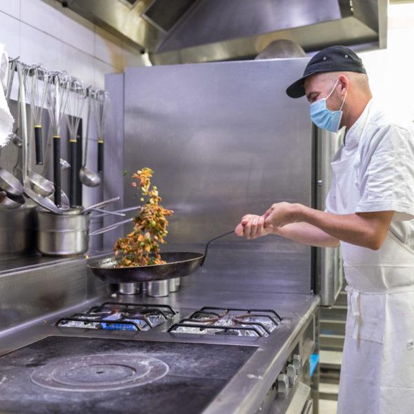 Un cuisinier fait sauter une poêlée de champignons au dessus du piano / A cook sautéing a pan of mushrooms above the piano