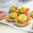 Mise en place à l'aide d'une pince à épiler d'un batonnet de ciboulette sur une galette quinoa petits légumes / Using tweezers, place a stick of chives on a small vegetable quinoa cake