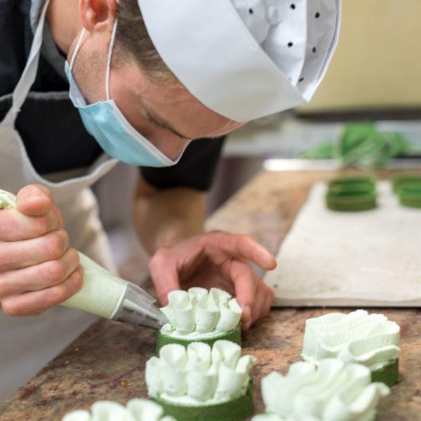 le chef pâtissier termine la couverture d'une tartelette pistache / the pastry chef finishes the cover of a pistachio tartlet