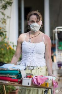 une femme masquée pose devant une tablette chargée de matière première utile à la confection de masques