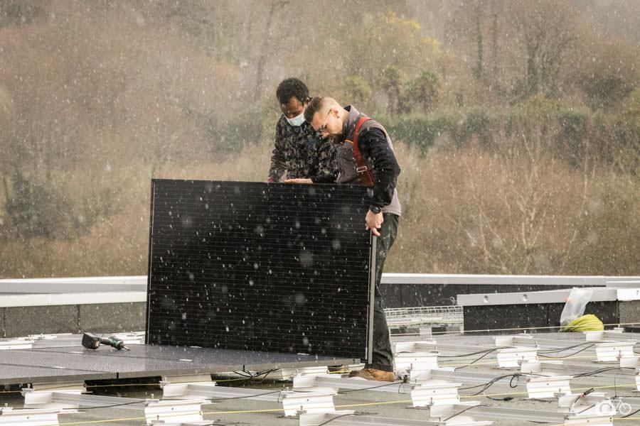 deux monteur positionnent un panneau solaire sur le toit d'un bâtiment